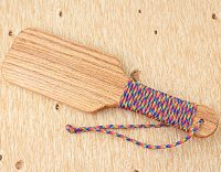 single hairbrush paddle wrapped in rainbow paracord