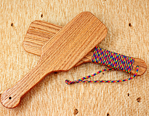 two wooden paddles in the shape of hairbrush backs overlapping, one with a bare wooden handle and the other with a paracord wrapped handle on a pine wood background