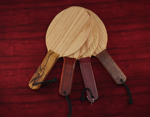 Selection of wooden paddles that look like ping pong paddles on red wooden background