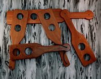 multiple wooden paddles with holes in paddle stacked on gray wooden background