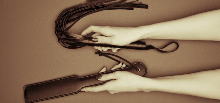 feminine hands holding leather paddle and flogger in sepia tones