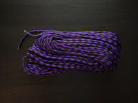 purple and black paracord on dark brown background