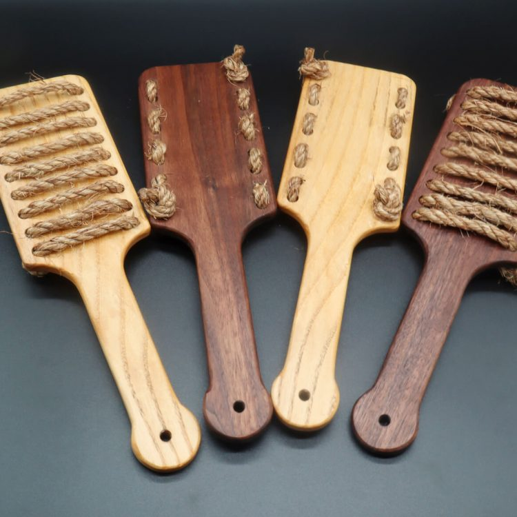 Four rough rider paddles side by side; two show the front side with the horizontal rope lines and two show the back with the rope knots. Two are made of ash. Two are made of black walnut.