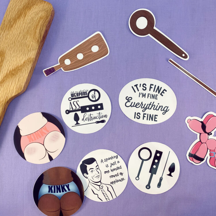 several styles of kinky die cut stickers next to wooden paddle