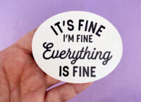 white hand holding white oval sticker with black text that says it's fine i'm fine everything is fine