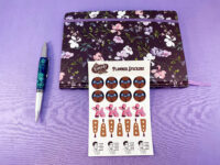 black kinky butt sticker variety pack next to floral journal on purple background