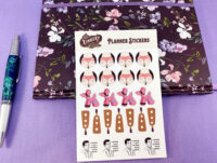 white kinky butt planner sticker variety sheet next to floral planner over purple background