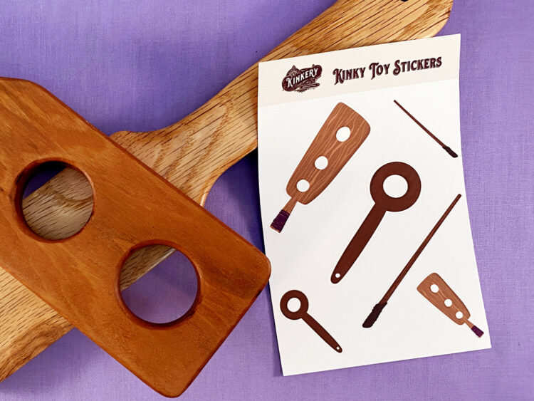 kinky toy sticker sheet next to two wooden paddles