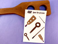 kinky toy sticker sheet leaning against holy terror paddle on purple background