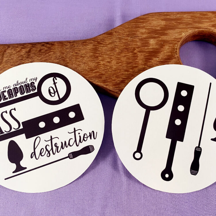 both text and non-text versions of weapons of ass destruction sticker leaning against wooden paddle over purple background