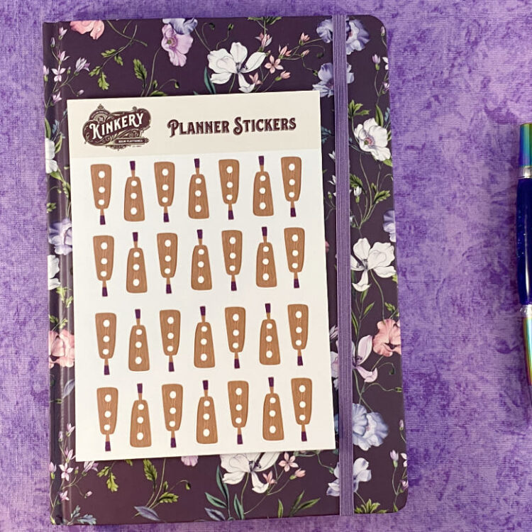 sheet of holy terror paddle planner stickers on top of floral purple planner next to turquoise pen on purple background