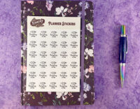 second view of it's fine planner sheet on top of purple floral planner next to turquoise pen on purple background