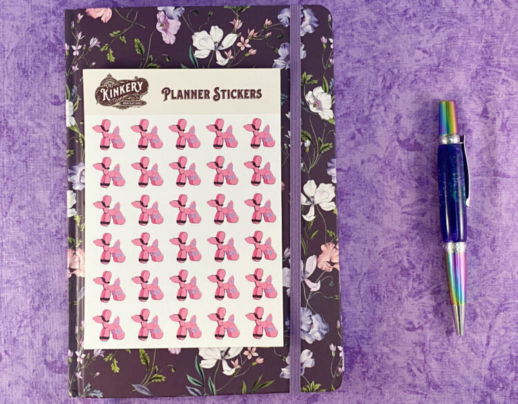 sheet of pink bondage balloon animal planner stickers on top of floral purple planner next to turquoise pen on purple background