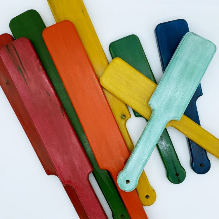 Stack of several pop-o-color paddles red, pink, orange, green, yellow, aqua, turquoise, blue
