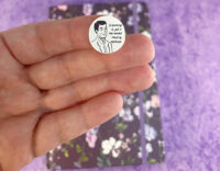 Kayla's hand holding a single one handed round of applause planner sticker to show detail and scale. Sticker on on index finger. In the background is a purple floral planner on a purple background.