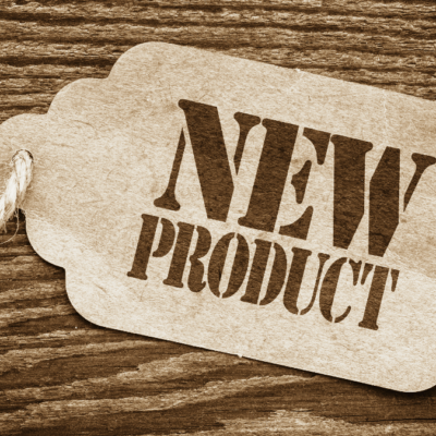 sepia toned image of tag that says new product with rope-like string attached on wooden background as a concept for new products from the kinkery