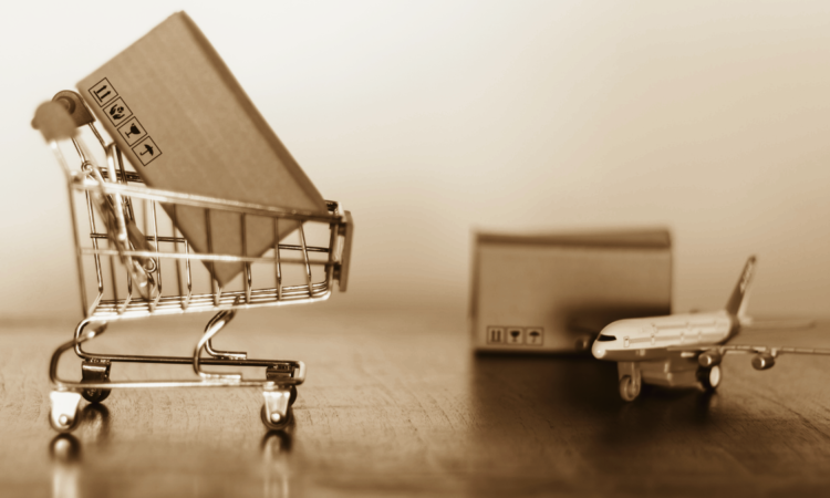 box in shopping cart and box next to airplane as concept for international shipping