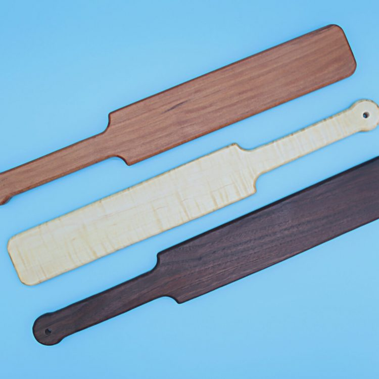 group of three large wooden paddles, from top to bottom: cherry, curly maple, and black walnut