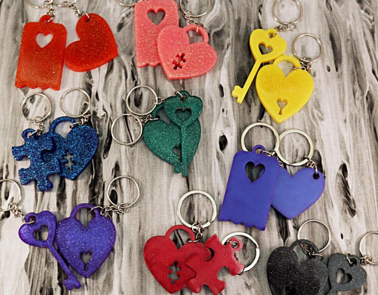 Array of dynamic keychain sets in multiple colors: Top row, left to right: orange heart, pink puzzle piece, yellow lock and key; Middle row, left to right: blue puzzle piece, geren lock and key, blurple heart; Bottom row, left to right: purple lock and key; red lock and key; black lock and key