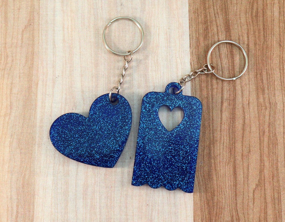 Two keychains in blue resin with blue glitter; on left, heart, on right, scallop-edged rectangle with small heart cut-out