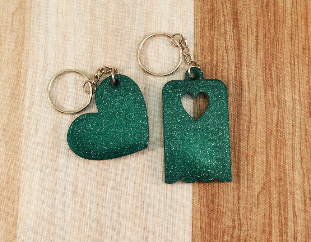 Two keychains in green resin with green glitter; on left, heart, on right, scallop-edged rectangle with small heart cut-out