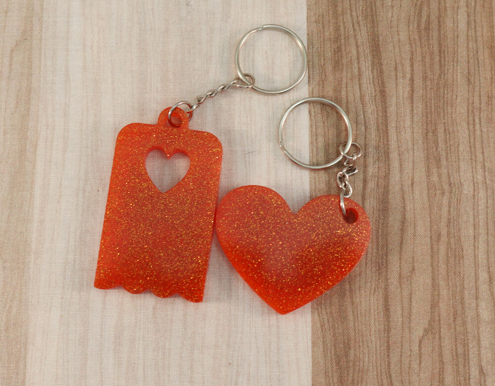 Two keychains in orange resin with orange glitter; on left, heart, on right, scallop-edged rectangle with small heart cut-out
