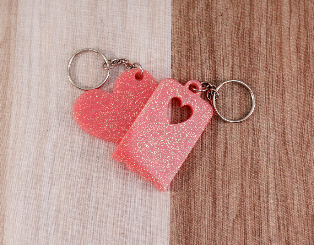 Two keychains in pink resin with multi-colored glitter; on left, heart, on right, scallop-edged rectangle with small heart cut-out