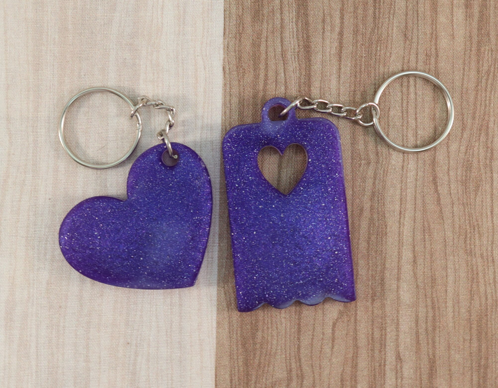 Two keychains in purple resin with purple glitter; on left, heart, on right, scallop-edged rectangle with small heart cut-out