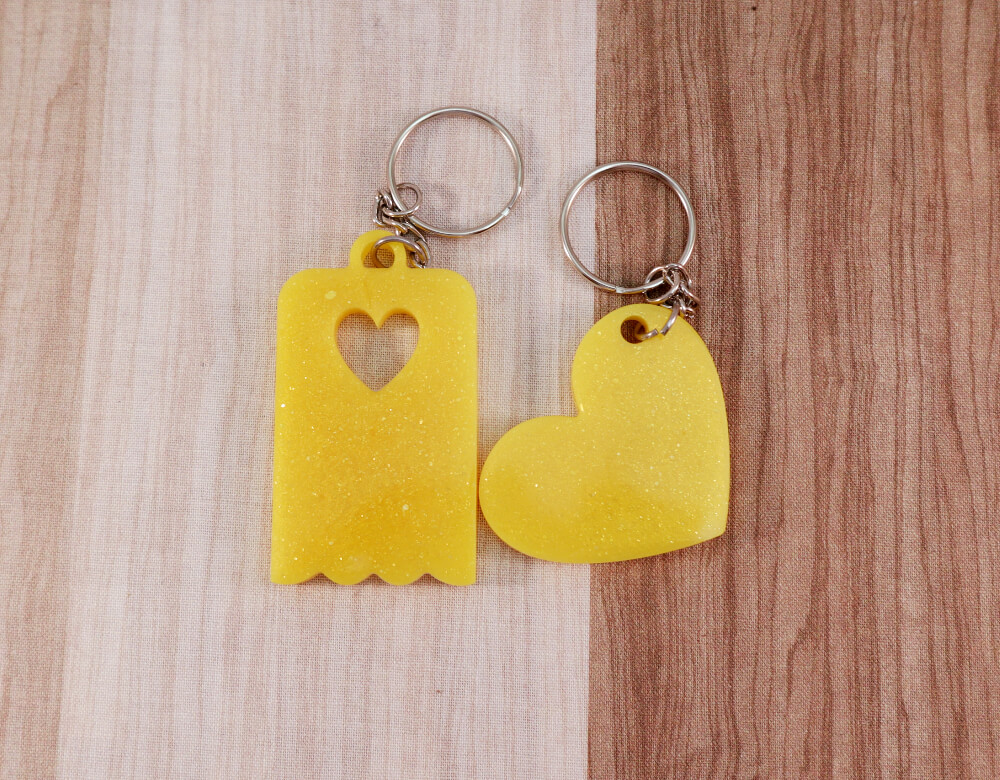 Two keychains in yellow resin with gold glitter; on left, heart, on right, scallop-edged rectangle with small heart cut-out