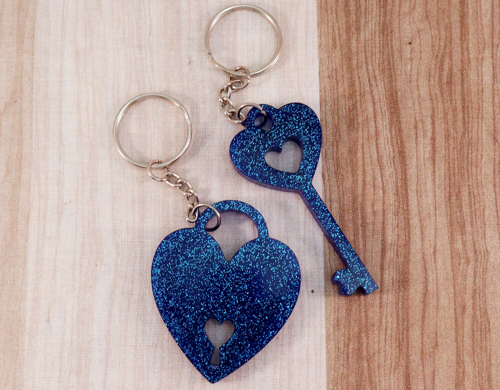two keychain set in blue resin with blue glitter; keychain on left is a key with a heart at the top; the keychain on the right is in the shape of a heart with a lock cut-out at the bottom