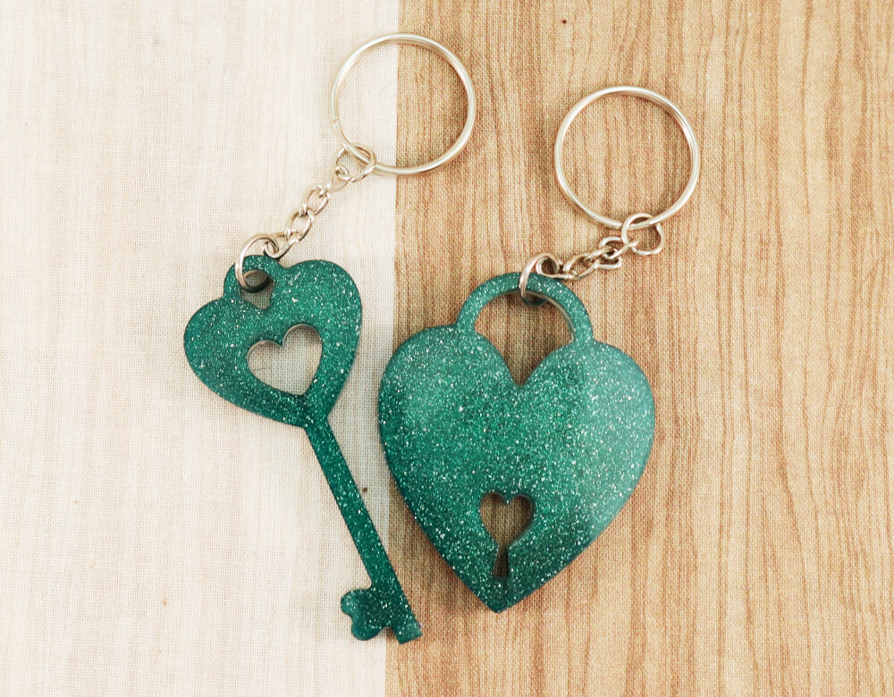 two keychain set in green resin with green glitter; keychain on left is a key with a heart at the top; the keychain on the right is in the shape of a heart with a lock cut-out at the bottom