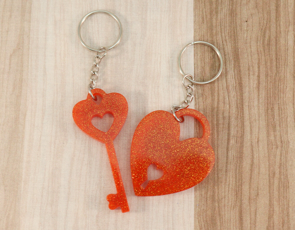 two keychain set in orange resin with orange glitter; keychain on left is a key with a heart at the top; the keychain on the right is in the shape of a heart with a lock cut-out at the bottom