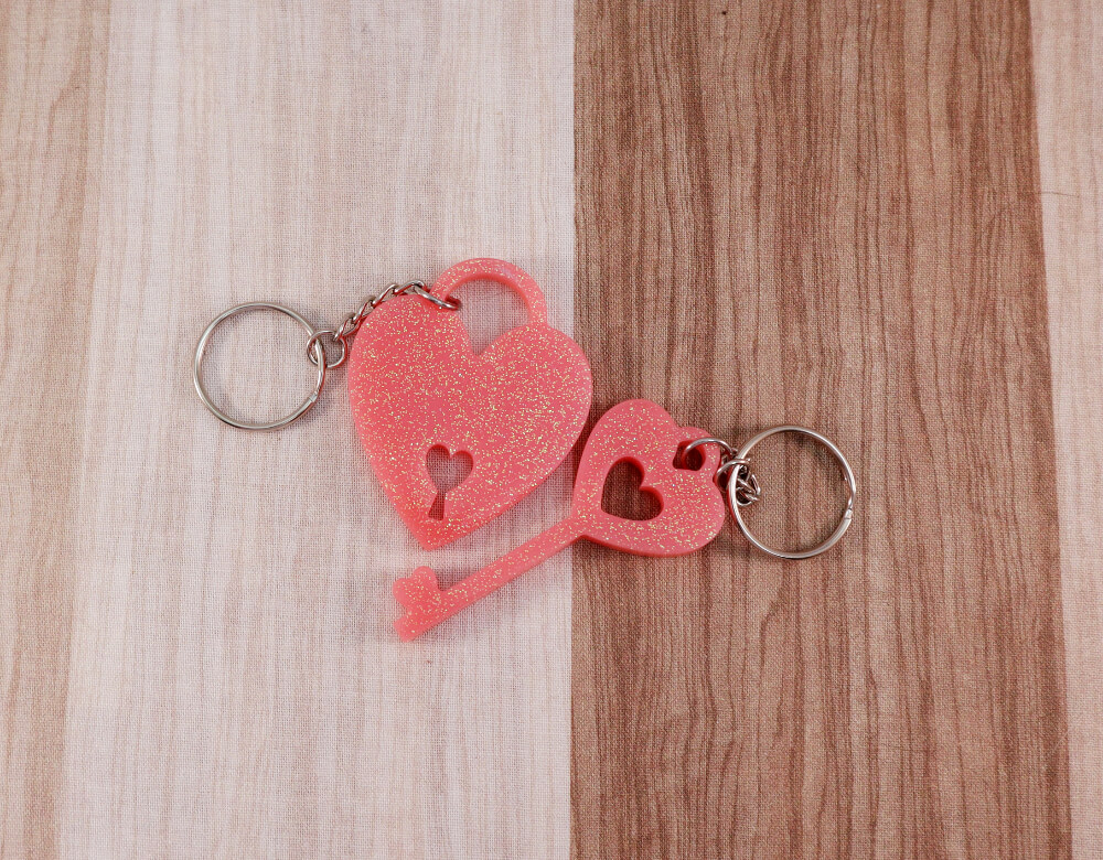 two keychain set in pink resin with multi-colored glitter; keychain on left is a key with a heart at the top; the keychain on the right is in the shape of a heart with a lock cut-out at the bottom