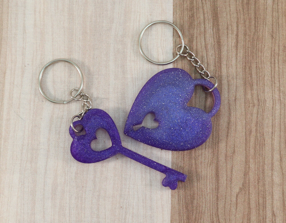 two keychain set in purple resin with purple glitter; keychain on left is a key with a heart at the top; the keychain on the right is in the shape of a heart with a lock cut-out at the bottom