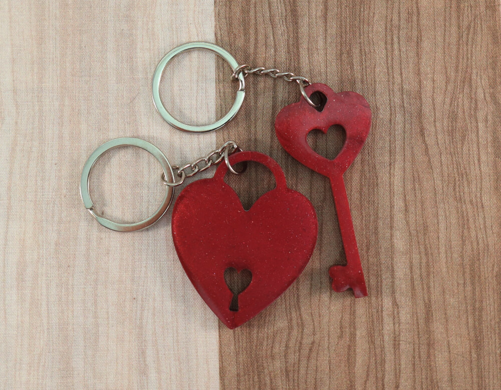 two keychain set in red resin with ruby glitter; keychain on left is a key with a heart at the top; the keychain on the right is in the shape of a heart with a lock cut-out at the bottom