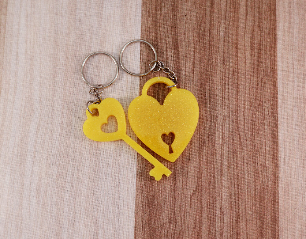 two keychain set in yellow resin with gold glitter; keychain on left is a key with a heart at the top; the keychain on the right is in the shape of a heart with a lock cut-out at the bottom