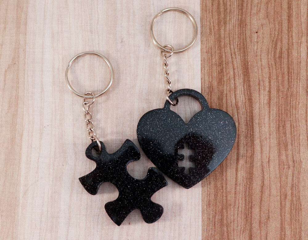 two keychain set in black resin with silver glitter; keychain on left is a puzzle piece; keychain on right is a heart lock with a puzzle piece cut-out