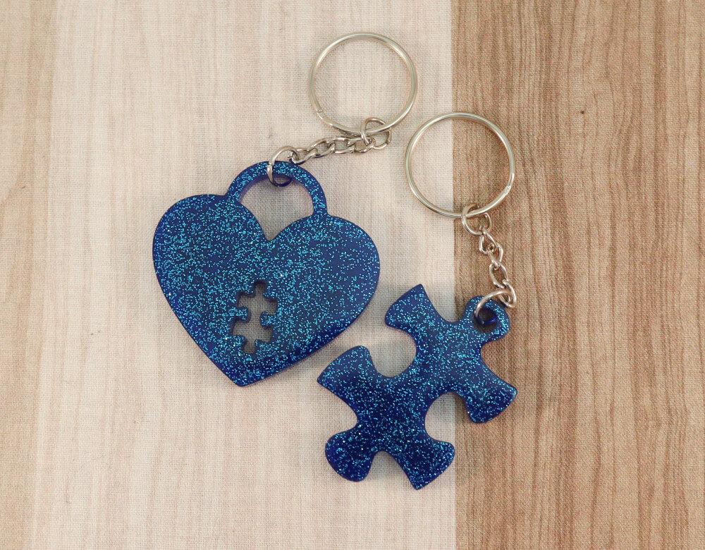 two keychain set in blue resin with blue glitter; keychain on left is a puzzle piece; keychain on right is a heart lock with a puzzle piece cut-out