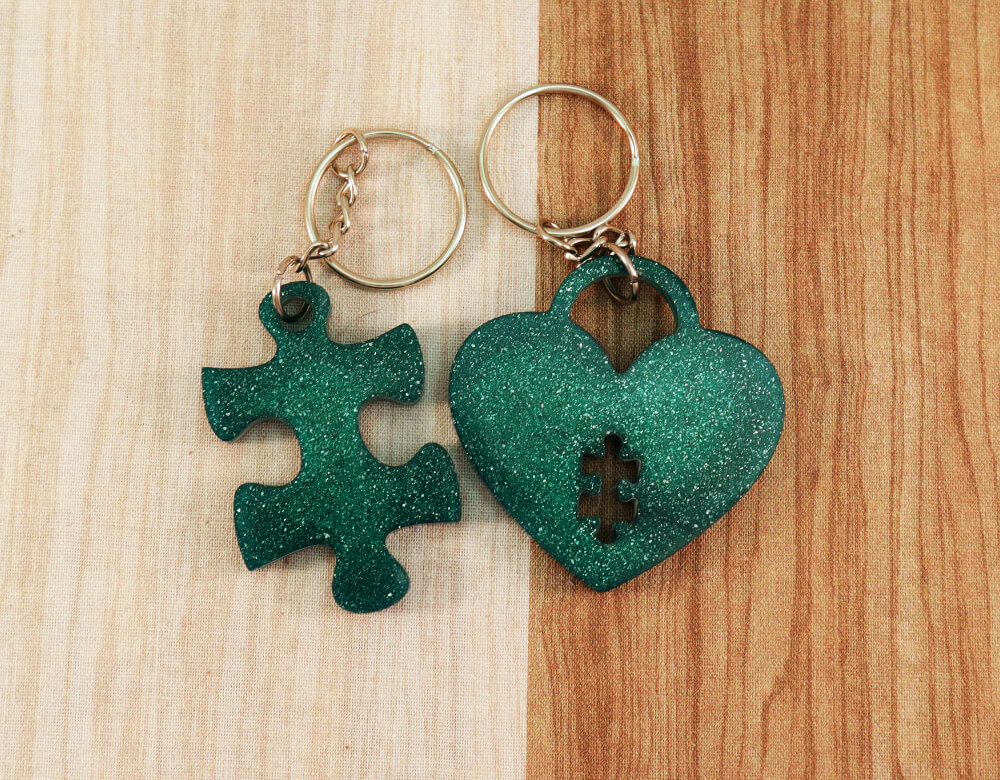 two keychain set in green resin with green glitter; keychain on left is a puzzle piece; keychain on right is a heart lock with a puzzle piece cut-out