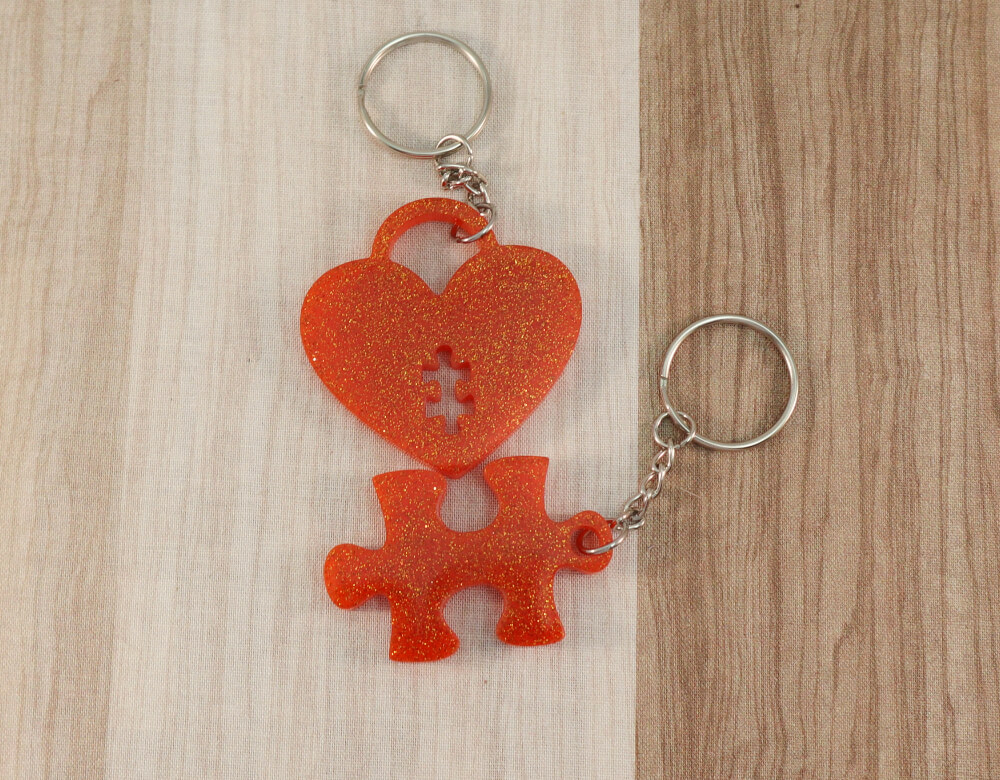 two keychain set in orange resin with orange glitter; keychain on bottom is a puzzle piece; keychain on top is a heart lock with a puzzle piece cut-out