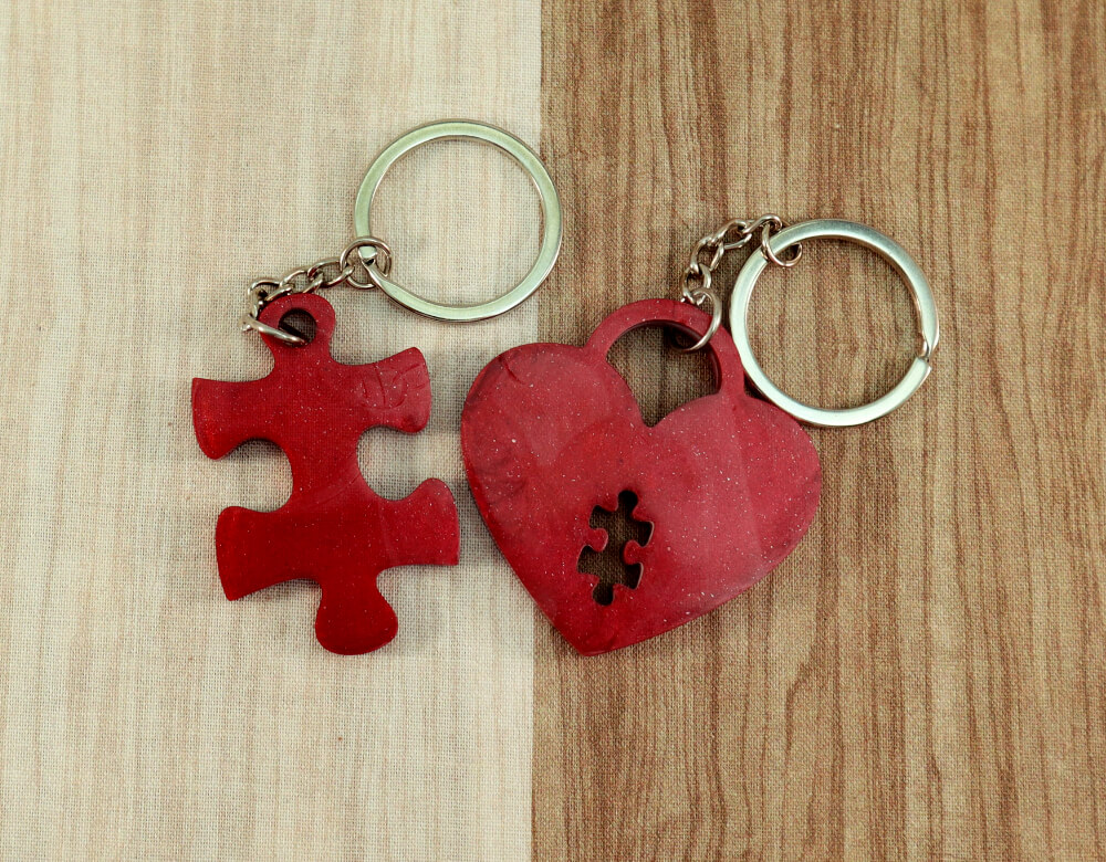 two keychain set in red resin with ruby glitter; keychain on right is a puzzle piece; keychain on left is a heart lock with a puzzle piece cut-out
