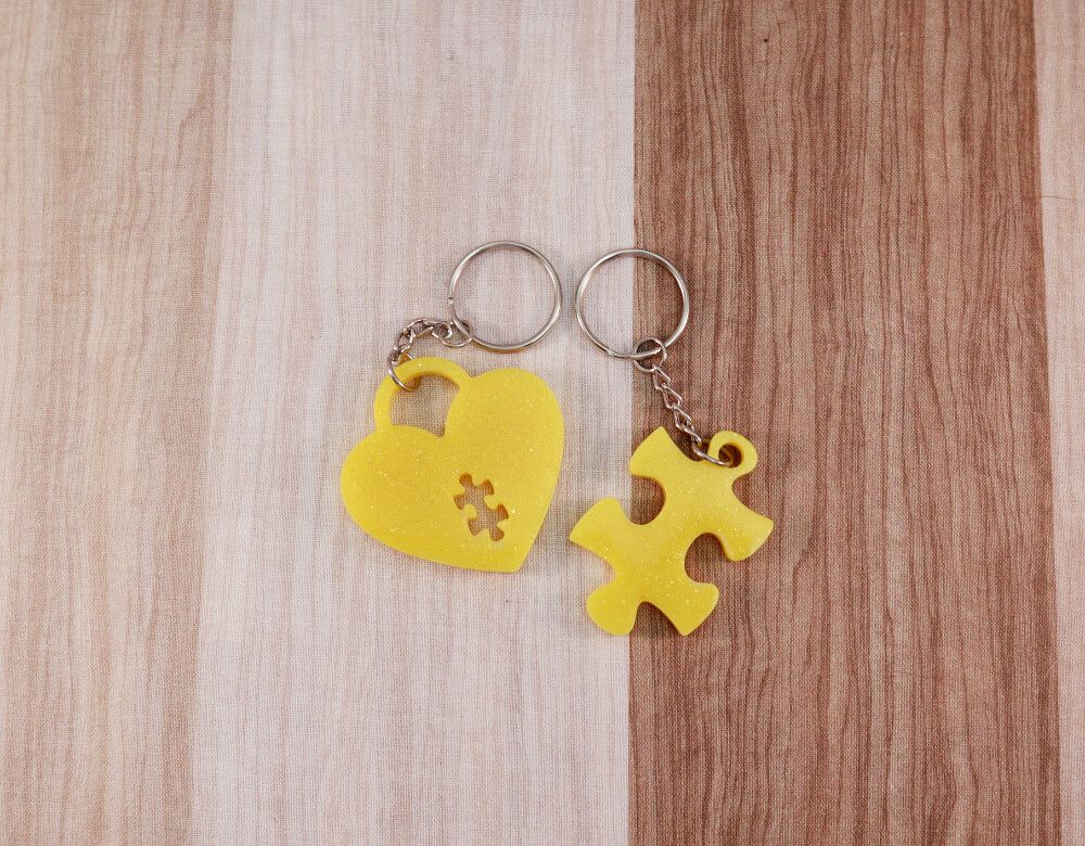two keychain set in yellow resin with gold glitter; keychain on right is a puzzle piece; keychain on left is a heart lock with a puzzle piece cut-out