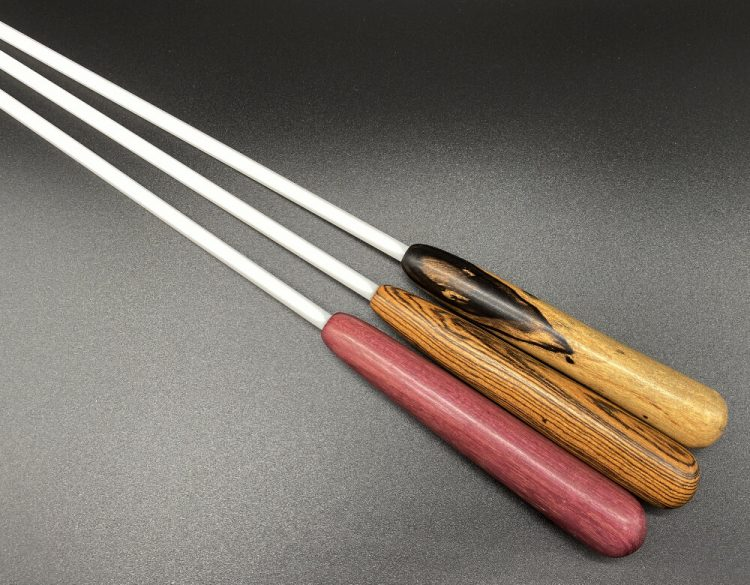 """close-up of three 1/4"""" white delrin cane with exotic wood handles; from left to right: ebony, purpleheart, and bocote"""