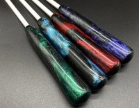 """four 1/4"""" white delrin canes with resin handles; colors from left to right: green and black, blue and black, red and black, and purple and black"""