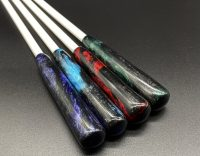 """four 3/8"""" white delrin canes with resin handles; colors from left to right: purple and black, blue and black, red and black, green and black"""