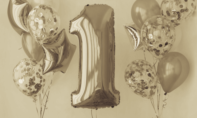 sepia tone photograph of balloon in the shape of a one and other helium balloons in the background